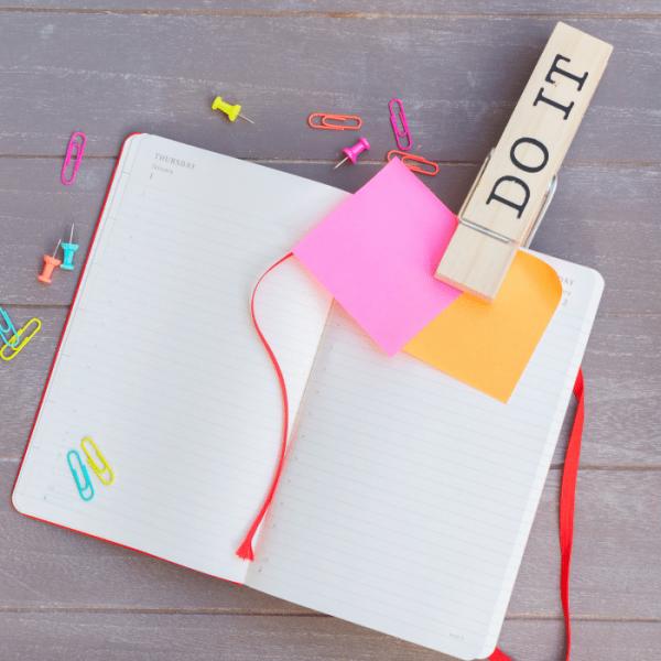 Motivationsbild mit dem Spruch do it auf einer Klammer, die auf einem Notizbuch steckt